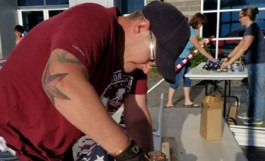 CWI student Dallas Hulsey helps assemble flags for the Eagle Field of Honor.