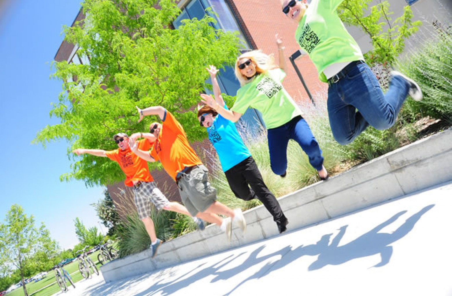 Five students jumping for a photo in front of Nampa Campus Academic Building