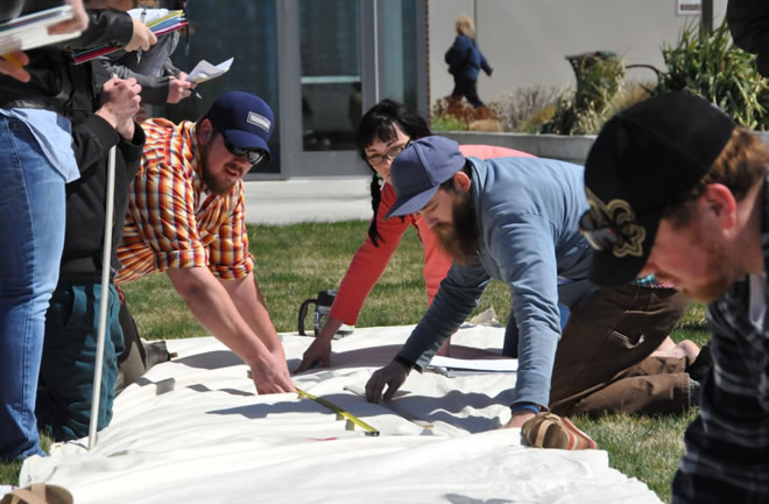 Students measuring dinosaur tracks on canvas on front lawn of Nampa Campus Academic Building in geology class
