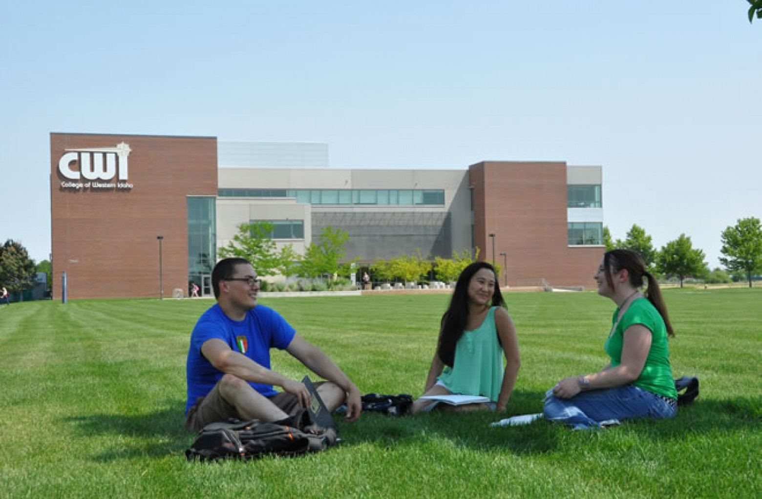 Three students chatting on front lawn of Nampa Campus Academic Building