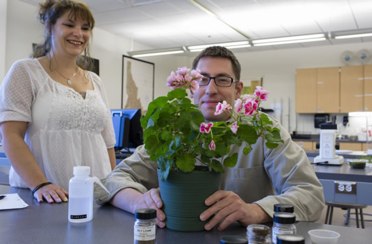 Two students testing flower pot soil in agriculture science lab